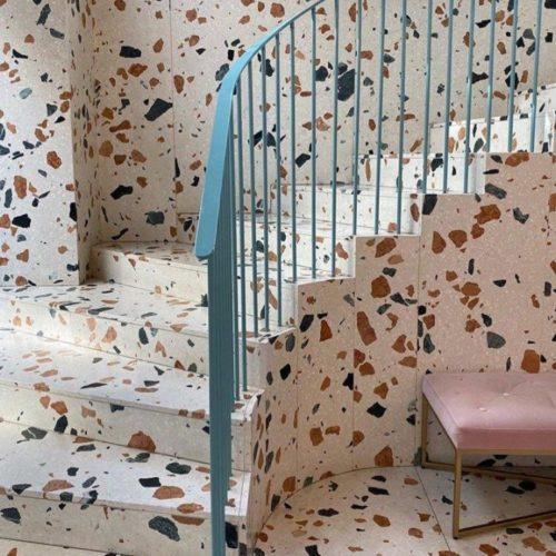 escada, parede lateral e piso revestido de porcelanto fundo claro imitando Granilitecom estampa maxi granilite