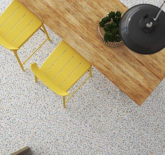 Porcelanato da coleção TESOURO PERDIDO, cor branco da Ceusa para a Amoedo Design. no piso, embaixo de uma mesa de madeira e cadeiras amarelas