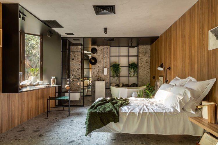 Quarto com madeira revestindo a parede da cama , piso porcelanato Granilite no quarto e do banheiro