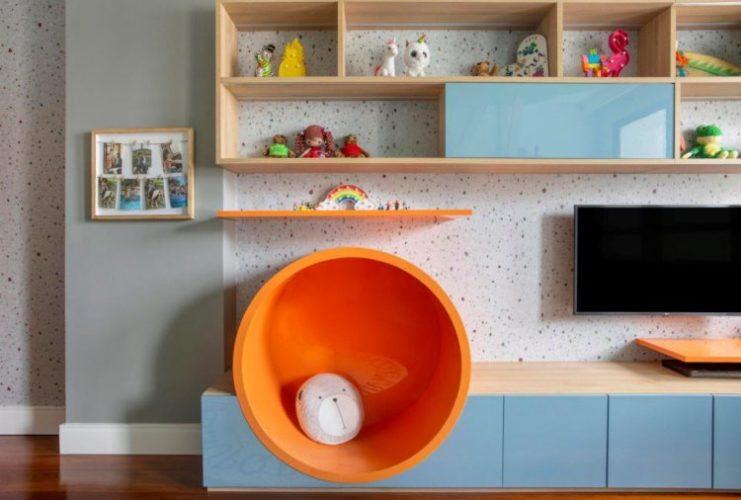 Brinquedoteca assinada pelo Studio Livia Amendola com papel de parede estampa Granilite. / Foto: Raiane Medina. Bnacada com um circulo laranja em madeira
