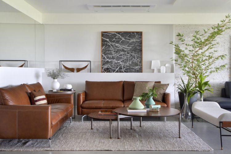 Sala clara, decorada com dois sofás em couro caramelo, duas mesas de centro redondas com alturas diferentes