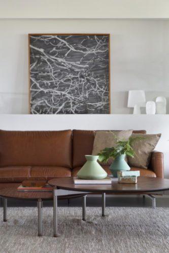 Sofá em couro caramelo e duas mesas de centro redondas na frente