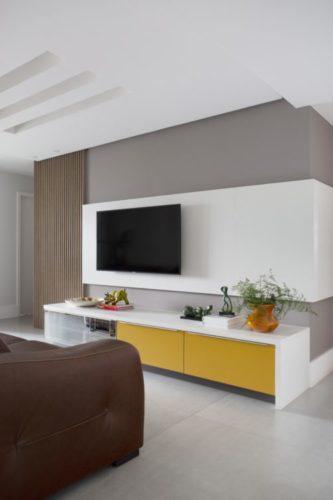 Parede pintada de cinza, um painel em madeira branca no meio para a tv e embaixo um rack branco e amarelo