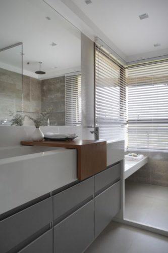 Bancada branca e armario embaixo na cor cinza no banheiro