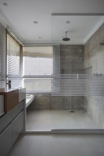 Box do chuveiro bem grande , meio ainel em vidro laminado separando e todo o banheiro revestido em porcelanto cinza