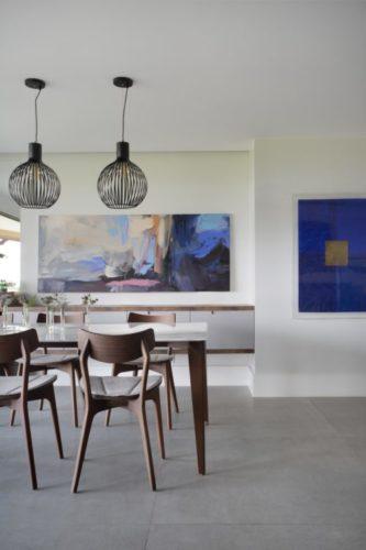 Sala com piso em porcelanto cinza e paredes brancas com duas telas na cor azul