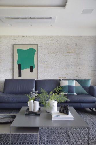 parede de tijolinho branco, sofá em couro azul na frente