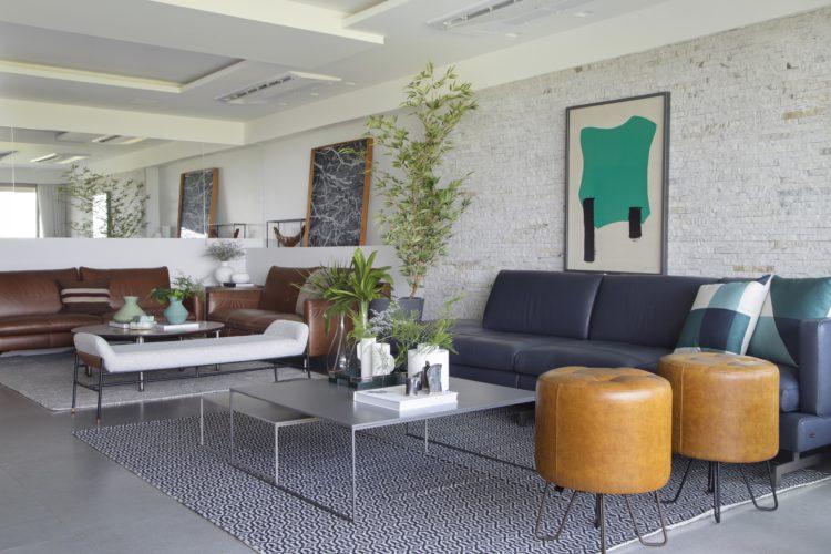 Clara e ampla a sala com dois ambientes, parede de tijolinho branco com sofá em couro azul em frente, dois banquinhos em couro caramelo ao lado. Ao fundo dois sofás de couro caramelo