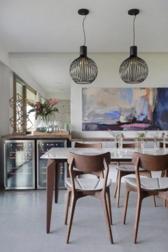 mesa de jantar e cadeiras em madeira, pendentes redondos em cima e ao fundo duas geladeiras de vinho embutidas no aparador