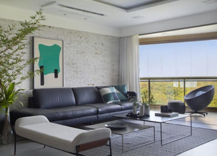 Apartamento na Barra de 288m2 com vista deslumbrante para a Lagoa de Marapendi. Varanda fechada com cortina de vidro, parede de tijolinho branco e sofá em couro azul em frente.