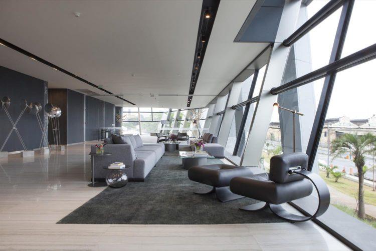 2017 Casa Cor Rio - Edifício AQWA. Imagem no lobby com as janelas do piso ao teto. Movies de design e cores cinzas decoram ao ambiente