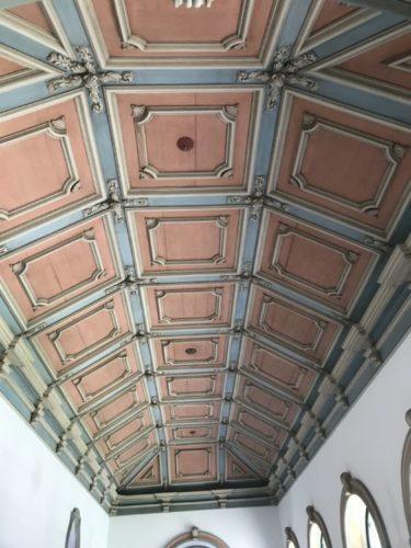 Teto de uma casa antiga todo trabalhado em madeira, fla de quadrados ornamentados, pintado de rosa e azul