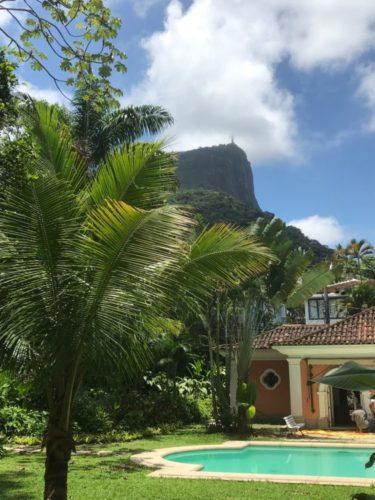 Um jardim de uma casa com piscina e coqueiros tendo o Cristo Redentor ao fundo