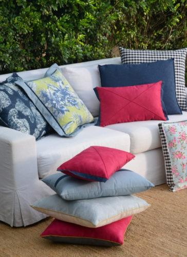 sofá branco com almofadas floridas e xadrez