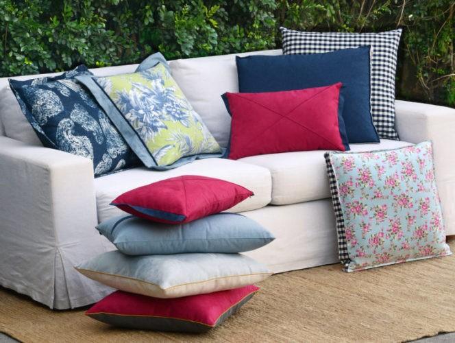 Coleção-cápsula de almofadas Conexão Décor + SttilloRio. Sofá branco com almofada floral, xadrez azul e jeans