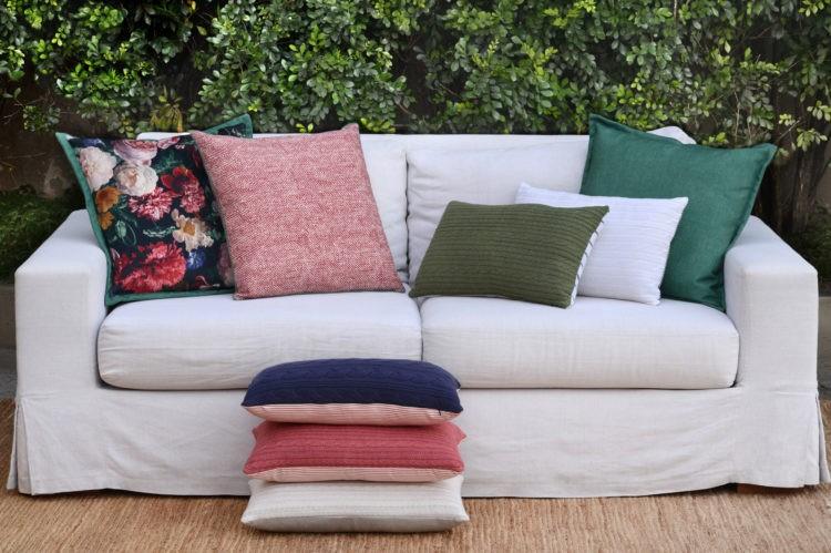 Coleção-cápsula de almofadas Conexão Décor + SttilloRio. Sofá branco com almofadas lisas e floral