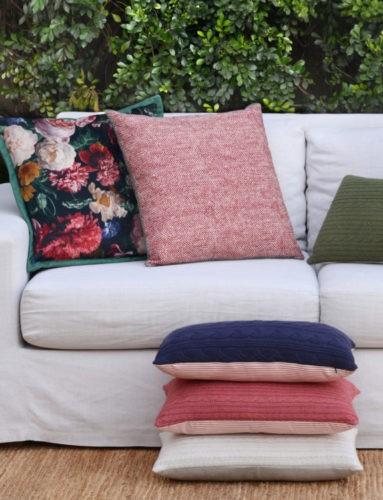 Almofadas floral, lisas e de tricot em cima do sofá.