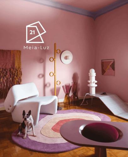 As cores de 2021 eleitas pelas Tintas Suvinil meia Luz, um rosinha. Sala com as paredes nessa cor e um tapete redonso com tons rosa