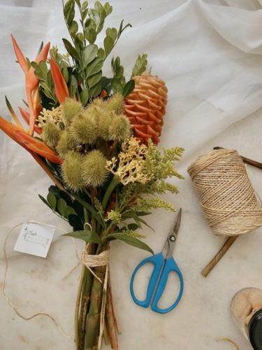 Arranjo de flor tropical, enrolado com barbante e ao lado o rolo do barbante e uma tesoura