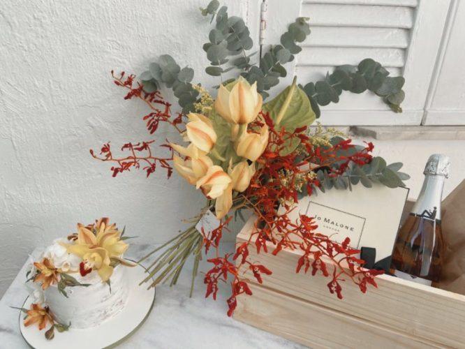 Caixa montada com vinho, arranjo de flores e um bolo
