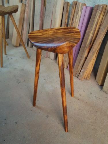 Banco sela do designer carioca Ricardo Graham, em madeira. Assento que lembra uma sela de cavalo e tres pés finos