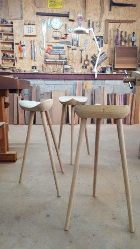 Banco sela do designer carioca Ricardo Graham, em madeira freijó. Assento que lembra uma sela de cavalo e com tres pés finso