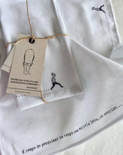 Guardanapos de linho branco um frase de Carlos D de Andrade bordada junto com um bonequinho da imagem do poeta