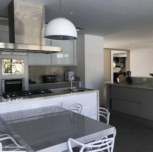 Cozinha aberta, bancada com cooktopo e coifa, Atras microondas e forno embutido na coluna