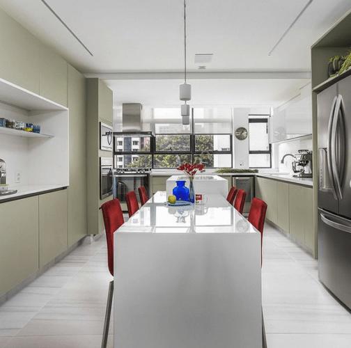 Cozinha clara e grande. Um bancada branca com cadeiras vermelhas no meio.