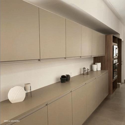 Cozinha com uma parede grande e armarios na cor bege na parte superior e na parte baixo, em toda a parede