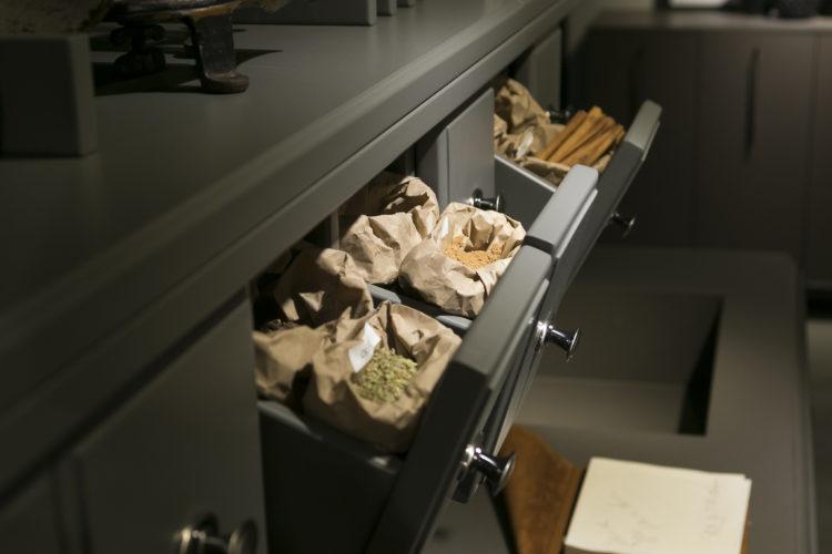 Armario de cozinha baixo na cor verde musgo e mini gavetas abertas com temperos.