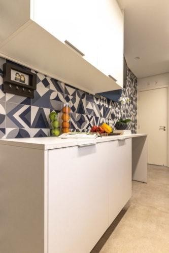 Parede da cozinha com azulejos estampados na cor azul e branca, com armarios em cima e embaixo na cor branca.