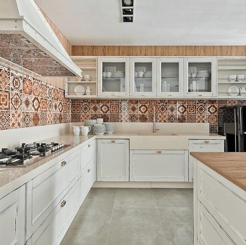 Cozinha grande e clara. Azulejos estampados na parede, armarios superioires com vidro transparente, armarios embaixo fechados a na cor branca.