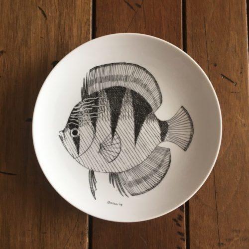 Pedras (e peixes) que encontrei pelo caminho. Prato raso em porcelana com peixe preto pintado a mão.