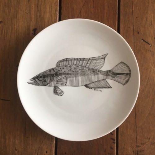 Pedras (e peixes) que encontrei pelo caminho. Prato raso redondo branco com peixe pintado de preto