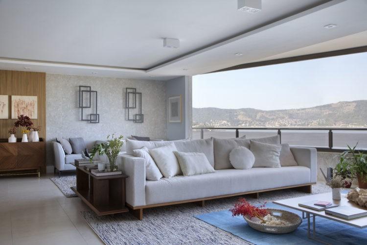 Apartamento de frente para o mar, vê-se o Museu de Arte Contemporânea com o Pão-de-Açúcar ao fundo. Sala integrada com a varanda, sofá claro e tapete azul