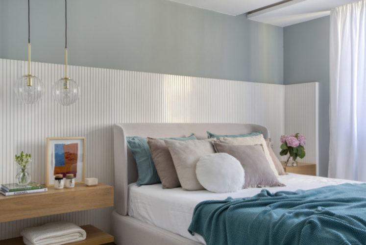 Quarto com meia parede revstida em madeira pintada de branco e ripada, em cima pintada de zul claro, Cama de casal com colcha turquesa
