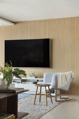 Tv na parede revestida em madeira ripada