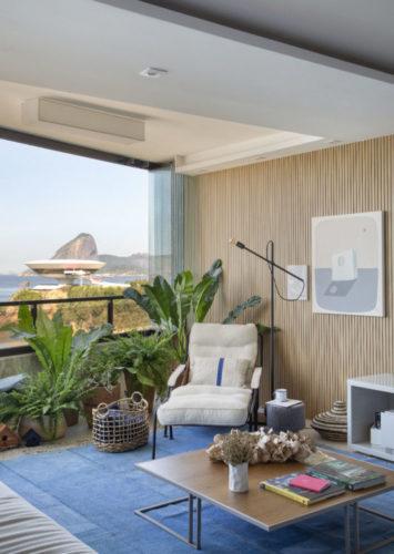 Apartamento de frente para o mar, vê-se o Museu de Arte Contemporânea com o Pão-de-Açúcar ao fundo. Sala integrada com a varanda, e muitos vasos de plantas ao longo