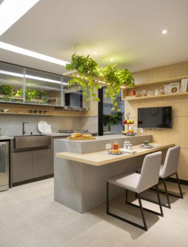 Cozinha na cor cinza e madeira, bancada alta e um aais baixa em madeira para refeicões.