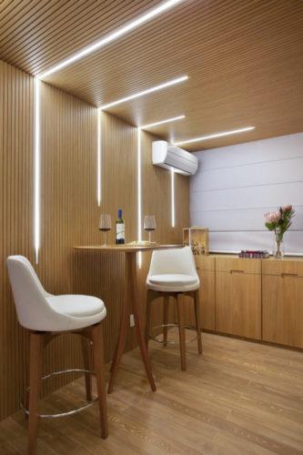 Parede e teto revestido em madeira ripada, mesa alta e duas banquetas altas brancas no espaço da adega.