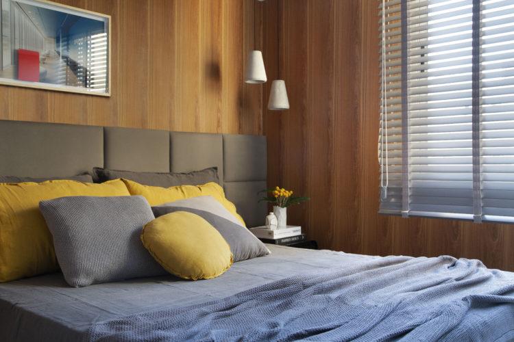 Quarto com paredes revestidas em madeira, cabeceira da cama em quadrados de tecido.