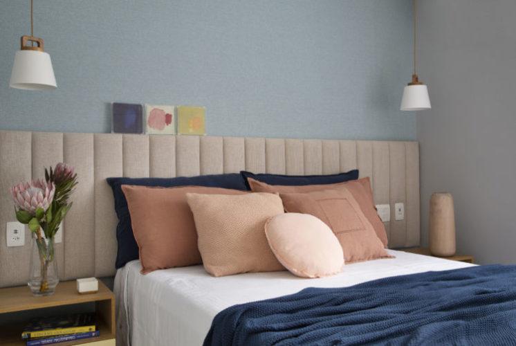 Cama de casal com cabeceira estofada com suede rosinha em meia parede, e em cima pintado de azul claro