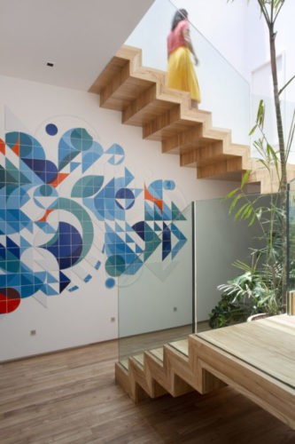 Escada em madeira, ligando dois andares da cobertura e na parede um painel de azulejos