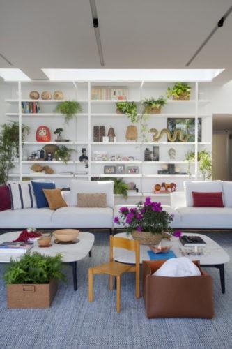 Sala com uma estante branca ao fundo repleto de objetos e na frente um sofá branco com almofadas colorids e tapete azul