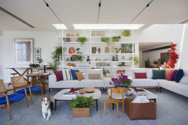 Mais do que inspiradas as arquitetas nessa projeto de cobertura duplex na Lagoa. Sala com tapete azul, sofá em L branco com almofadas coloridas e no fundo estante branca com objetos
