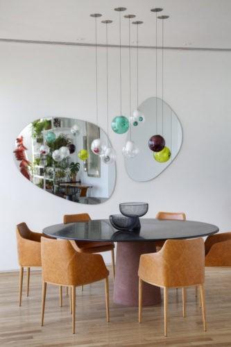 Mesa de jantar redonda, cadeiras em couro, espelhos com formato organico na parede e luminarias pendentes coloridas redondas.