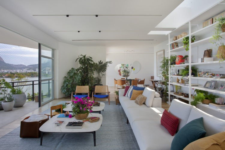 Ampla e clara sala de uma cobertura com varanda. Na sala sofá em L branco e almofadas coloridas
