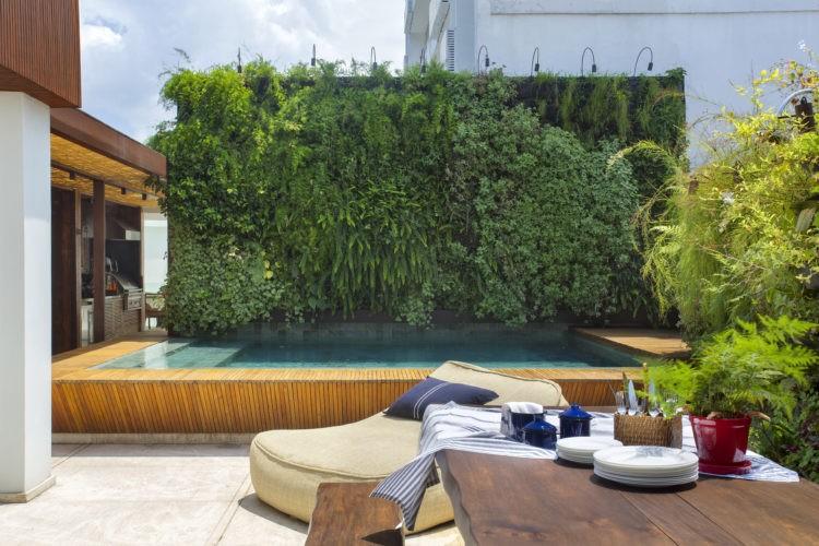 Espaço externo em uma cobertura com piscina, parede verde e uma mesa em madeira.