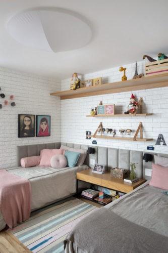 Quarto de menina com duas camas cinza com almofadas rosa e cabeceira em gomes de tecido em toda a volta. Parede de tijolinho branco